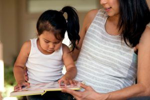 Young ethnic mother looking at a book with her daughter